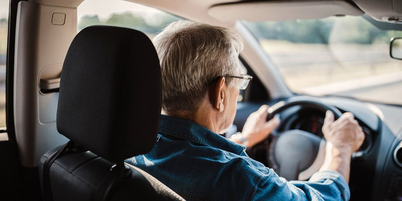 senior man with glasses driving