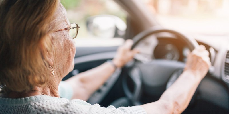 senior woman with glasses driving