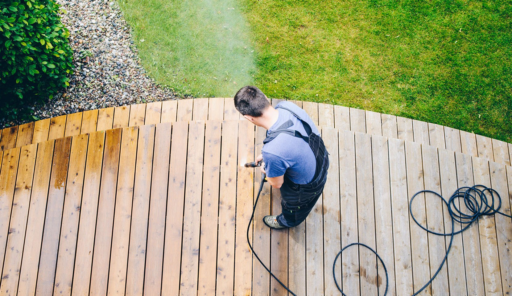 Man powerwashing an outdoor deck