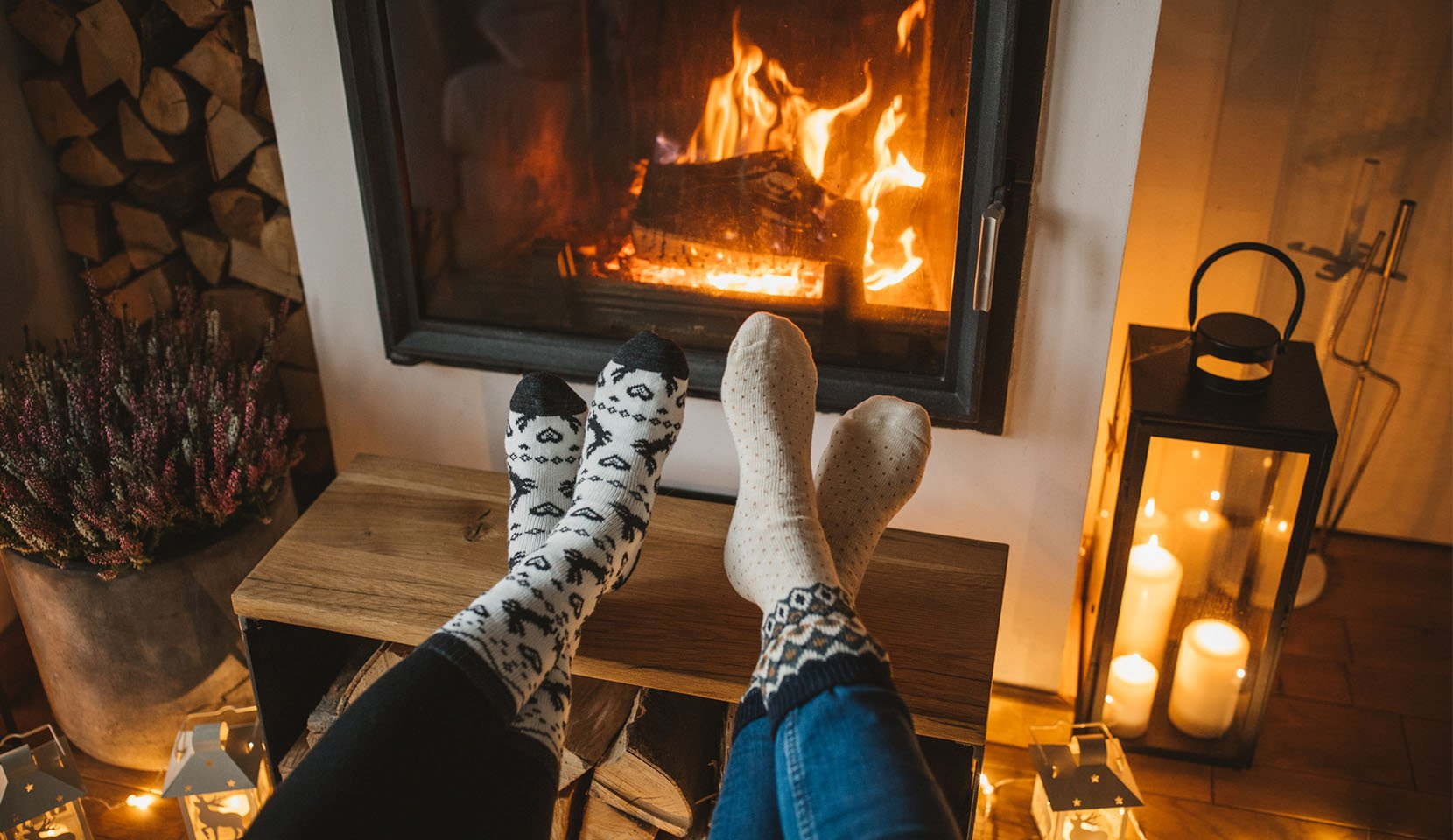 A couple warms their feet by the fireplace